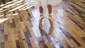 Bailarín de ballet joven en la danza blanca del ballet de las prácticas de los zapatos y de la falda de ballet en el piso de made almacen de video