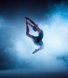 Bailarín de ballet joven hermoso que salta en un fondo de la lila Foto de archivo libre de regalías