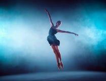 Bailarín de ballet joven hermoso que salta en un fondo de la lila Imagen de archivo