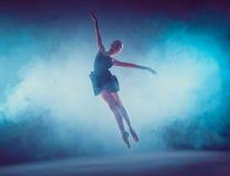 Bailarín de ballet joven hermoso que salta en un fondo de la lila Imágenes de archivo libres de regalías