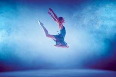 Bailarín de ballet joven hermoso que salta en un fondo de la lila Foto de archivo