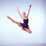 Bailarín de ballet joven hermoso que salta en un gris Imagen de archivo libre de regalías