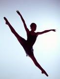 Bailarín de ballet joven hermoso que salta en un gris Fotografía de archivo