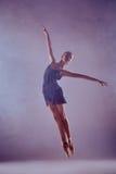Bailarín de ballet joven hermoso que salta en una lila Imagenes de archivo