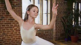 Bailarín de ballet joven que baila un ballet clásico en zapatos y tutú del pointe en el fondo de una ventana y de un rojo grandes almacen de metraje de vídeo