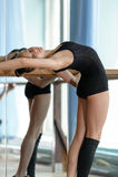 Bailarín de ballet joven que estira hacia fuera en la barra Foto de archivo