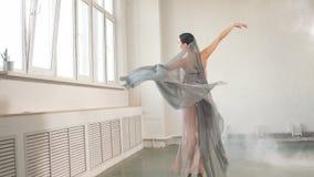 Bailarín de ballet moderno del estilo ex en un fondo gris del estudio en niebla almacen de video