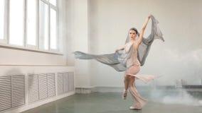 Bailarín de ballet moderno en traje que fluye escénico que se resuelve en el estudio, cámara lenta metrajes