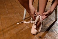 Bailarín de ballet que ata los deslizadores alrededor de su pointe de la bailarina de la mujer del tobillo fotos de archivo