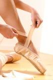 Bailarín de ballet que ata los deslizadores alrededor de su tobillo Imágenes de archivo libres de regalías