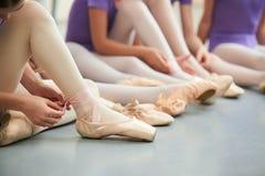 Bailarín de ballet que ata los deslizadores alrededor de su tobillo imagen de archivo
