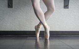 Bailarín de la bailarina en el pointe del en del estudio del ballet en la cuarta posición del releve imagen de archivo