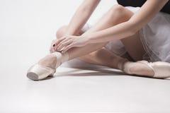 Bailarín de la bailarina que se sienta con sus piernas cruzadas Foto de archivo