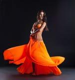 Bailarín de la belleza que presenta en traje anaranjado tradicional Foto de archivo libre de regalías