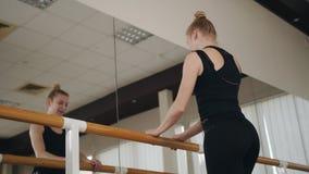Bailarín de la muchacha que calienta en el salón de baile en la barra del ballet metrajes