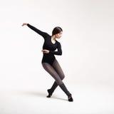 Bailarín de la mujer joven en la presentación negra del traje de baño Foto de archivo