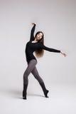 Bailarín de la mujer joven en la presentación negra del traje de baño Fotografía de archivo
