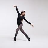 Bailarín de la mujer joven en la presentación negra del traje de baño Foto de archivo libre de regalías