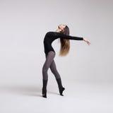 Bailarín de la mujer joven en la presentación negra del traje de baño Fotografía de archivo libre de regalías