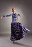 Bailarín de sexo femenino agraciado que presenta en vestido elegante Imagenes de archivo
