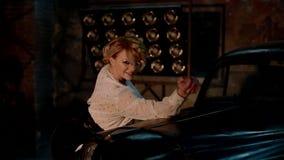 Bailarín de sexo femenino blanco joven en estudio cerca del coche retro almacen de metraje de vídeo