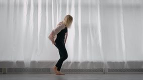 Bailarín de sexo femenino del estilo moderno profesional que ensaya por la ventana en estudio almacen de video