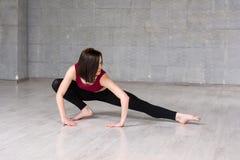 Bailarín de sexo femenino joven que estira en estudio Imágenes de archivo libres de regalías