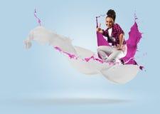 Bailarín de sexo femenino joven que salta con el chapoteo de la pintura Fotografía de archivo
