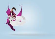 Bailarín de sexo femenino joven que salta con el chapoteo de la pintura Foto de archivo libre de regalías