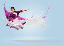 Bailarín de sexo femenino joven que salta con el chapoteo de la pintura Imágenes de archivo libres de regalías