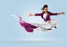 Bailarín de sexo femenino joven que salta con el chapoteo de la pintura Fotografía de archivo libre de regalías