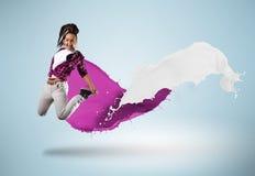 Bailarín de sexo femenino joven que salta con el chapoteo de la pintura Foto de archivo