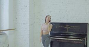 Bailarín de sexo femenino que habla en el teléfono móvil durante ensayo almacen de metraje de vídeo