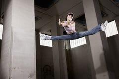Bailarín de sexo femenino que salta con los pulgares para arriba. Fotografía de archivo
