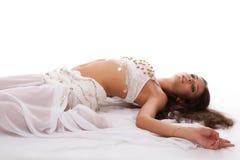 Bailarín de vientre árabe de la mujer en la mentira blanca del traje Fotografía de archivo