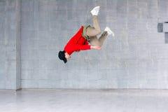 Bailarín del rap que salta en fondo gris Fotografía de archivo