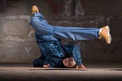 Bailarín del salto de la cadera en estilo moderno sobre la pared de ladrillo Foto de archivo libre de regalías