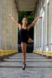 Bailarín delgado hermoso de la mujer de los deportes en un traje y un pointe negros Fotos de archivo