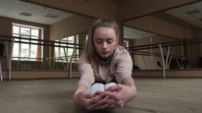 Bailarín flexible de la mujer joven que estira las piernas en estudio almacen de video