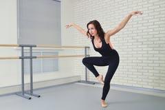 Bailarín hermoso de la mujer en el mono negro que baila agraciado ballet en el estudio Foto de archivo libre de regalías