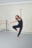Bailarín hermoso de la mujer en el mono negro que baila agraciado ballet en el estudio Foto de archivo