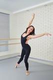 Bailarín hermoso de la mujer en el mono negro que baila agraciado ballet en el estudio Fotografía de archivo