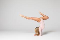 Bailarín hermoso joven de la gimnasia de mujer en el traje de baño rosado que presenta en un fondo gris claro del estudio Fotografía de archivo libre de regalías