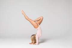 Bailarín hermoso joven de la gimnasia de mujer en el traje de baño rosado que presenta en un fondo gris claro del estudio Fotos de archivo libres de regalías