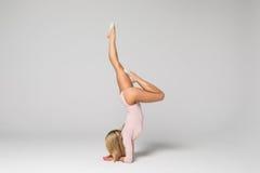 Bailarín hermoso joven de la mujer en el traje de baño rosado que presenta en un fondo gris claro del estudio Foto de archivo libre de regalías