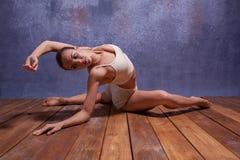 Bailarín hermoso joven en el baile beige del traje de baño Imagenes de archivo