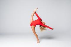 Bailarín hermoso joven en el traje de baño rojo que presenta en un fondo blanco del estudio Foto de archivo libre de regalías