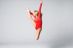 Bailarín hermoso joven en el traje de baño rojo que presenta en un fondo blanco del estudio Fotos de archivo