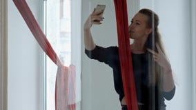Bailarín hermoso que toma el selfie usando smartphone con la seda aérea después de entrenamiento Imágenes de archivo libres de regalías
