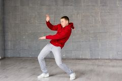 Bailarín joven lindo que presenta en fondo gris Foto de archivo